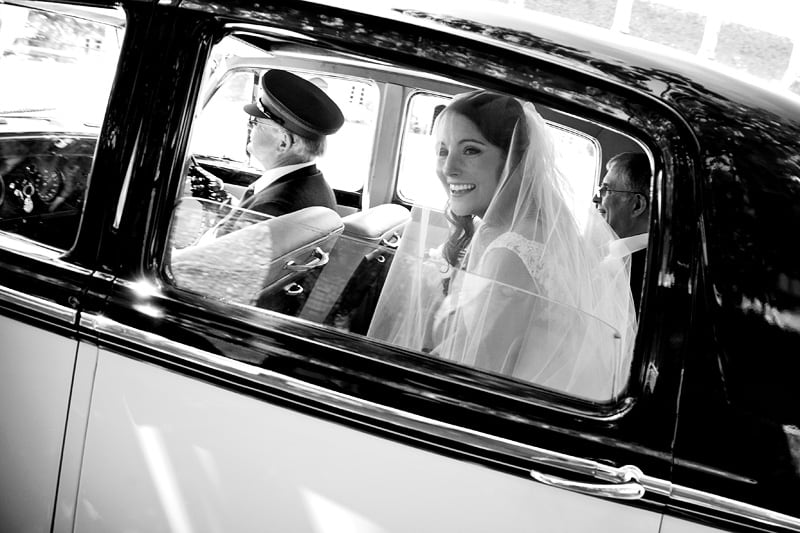 Bridebook.co.uk- bride smiling from inside of wedding car