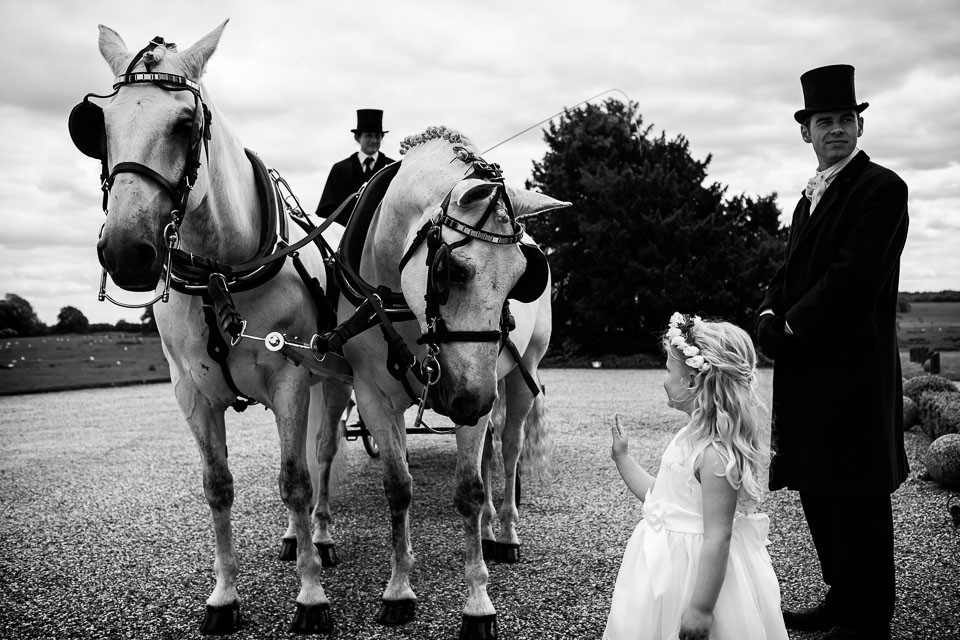 Bridebook.co.uk- flower girl waving up at the horse drawn carriage