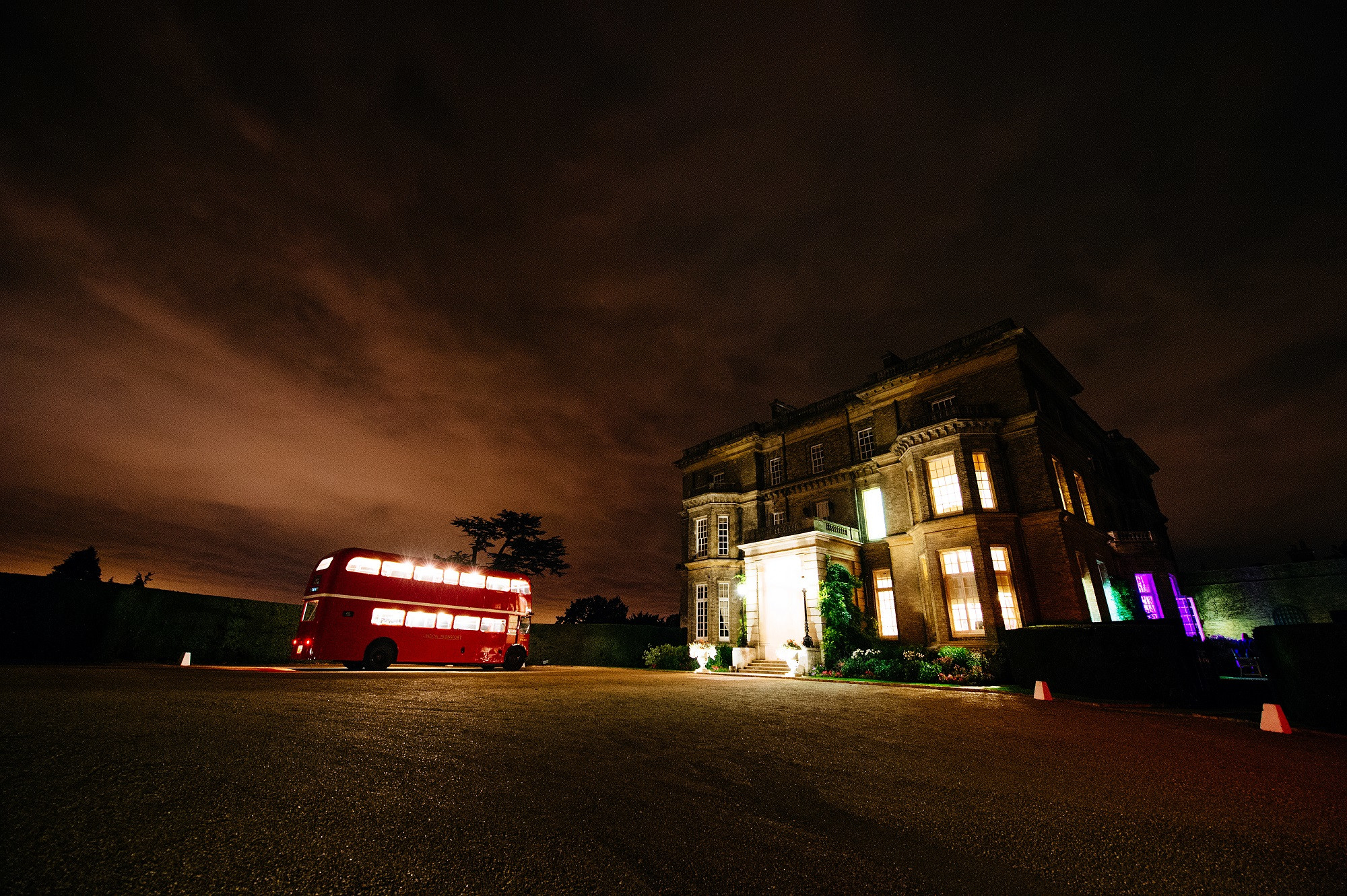 Bridebook.co.uk- wedding venue at night with a london bus parked in front