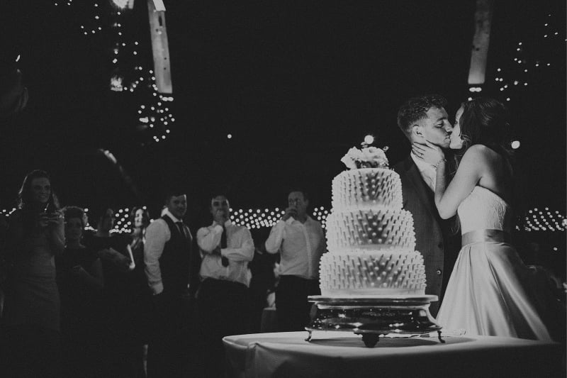 Bridebook.co.uk- bride and groom kiss in front of cake