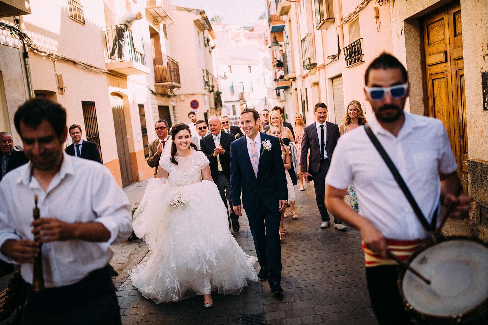 Bridebook.co.uk- bride groom and party walking behind musicians