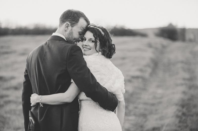 Bridebook.co.uk- groom and bride hug as bride looks behind her