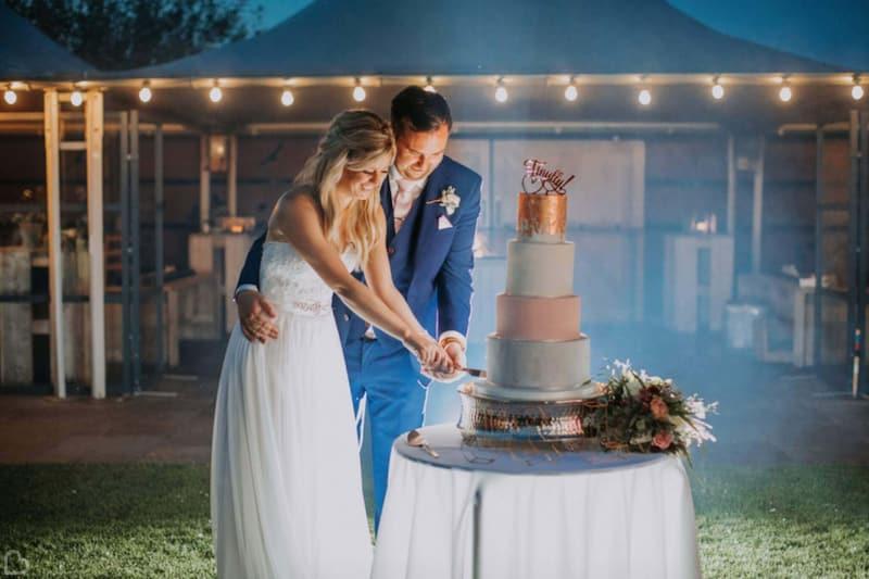 newlyweds cutting their wedding cake at southend barns wedding venue