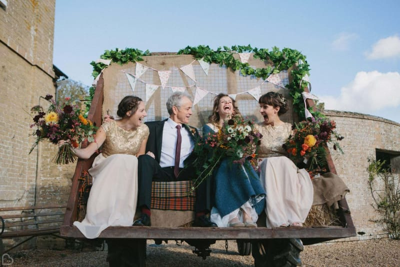 wedding guests laugh at the back of a truck in godwich great hall barn