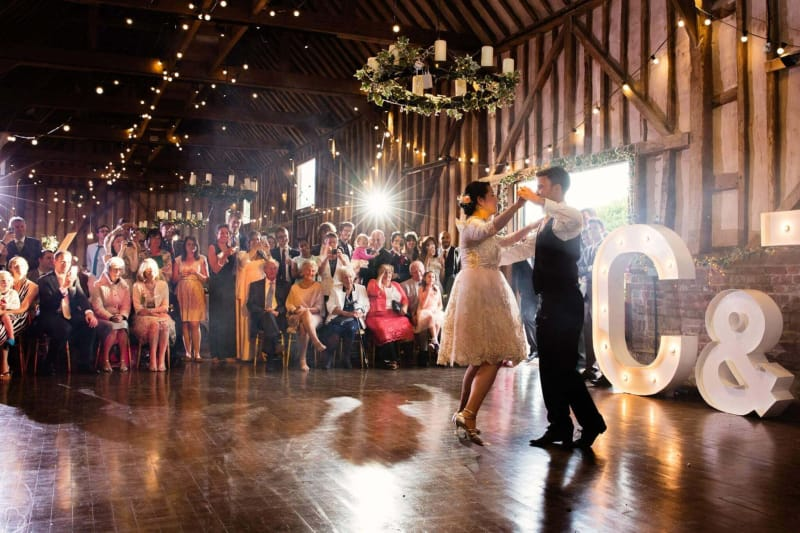 newlyweds perform their first dance as wedding guests cheer them on at lillibrooke manor