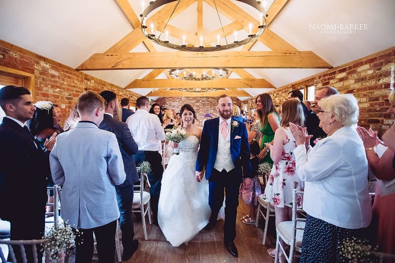 newlyweds exit their ceremony as guests cheer at apton hall wedding venue in essex