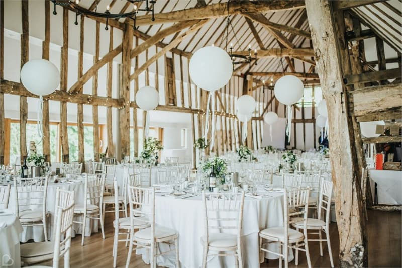 colville hall decorated with white circular lamps for a wedding, a barn venue in the uk