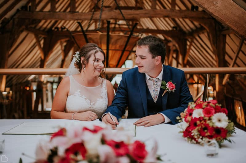 newlyweds signs their guest book at the barn in colchester