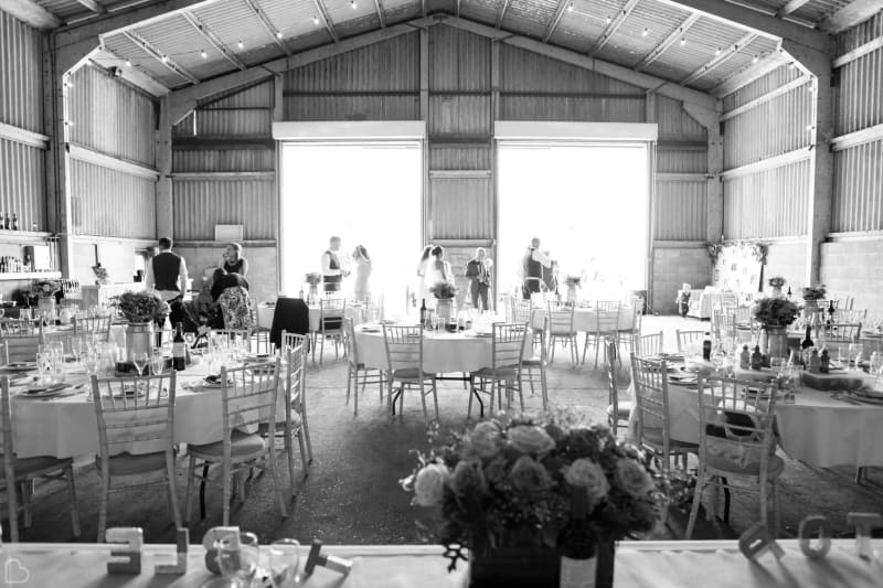 black and white photo of inside of the barns at lodge farm ready for a wedding