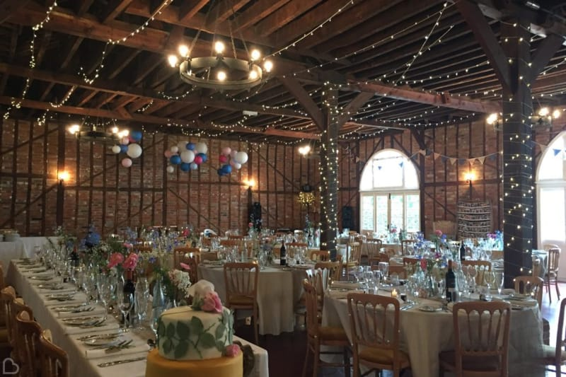 the coach house decorated with fairy lights for a wedding