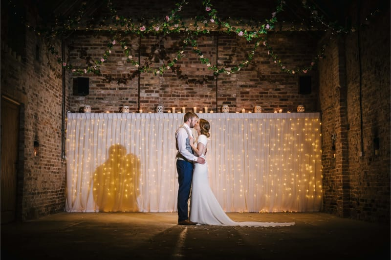 newlyweds kiss at barmyfield barns a barn wedding venue in york