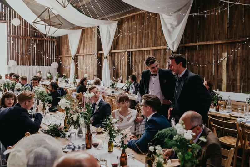 guests laugh and chatter at deepdale farm, a barn wedding venue in yorkshire