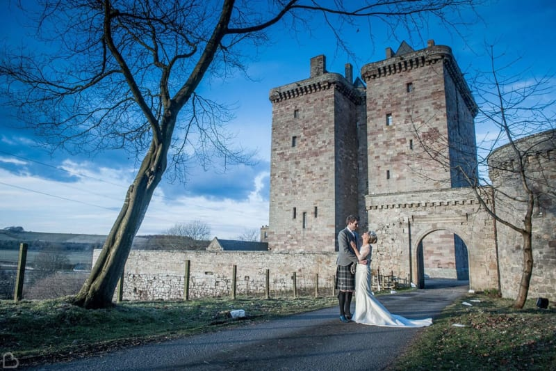 newlyweds pose in front of borthwick castle