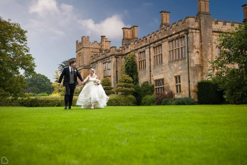 couple walks in front of sudeley castle, a wedding venue in the uk