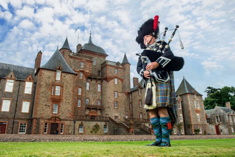 a scottish man plays the pipes in front of thirslestane castle