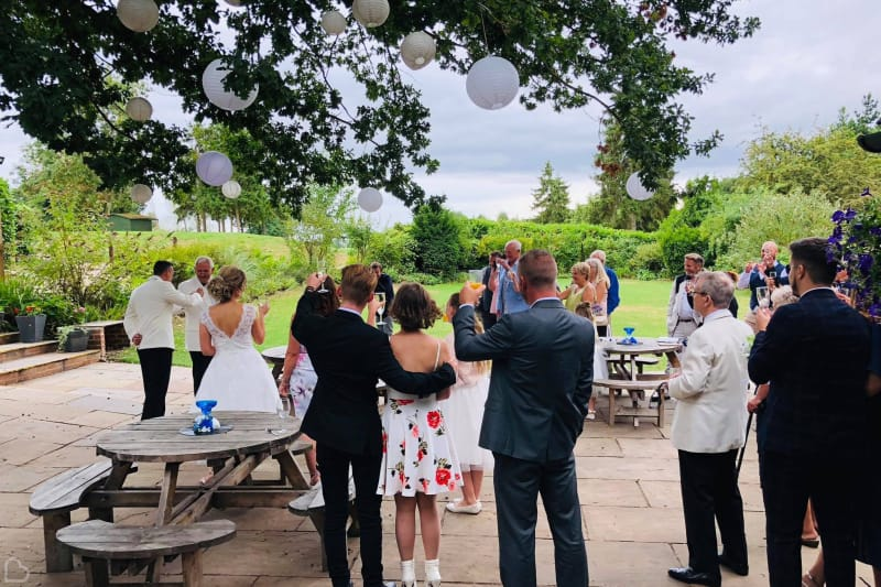 wedding guests toast outside in forrester park wedding venue