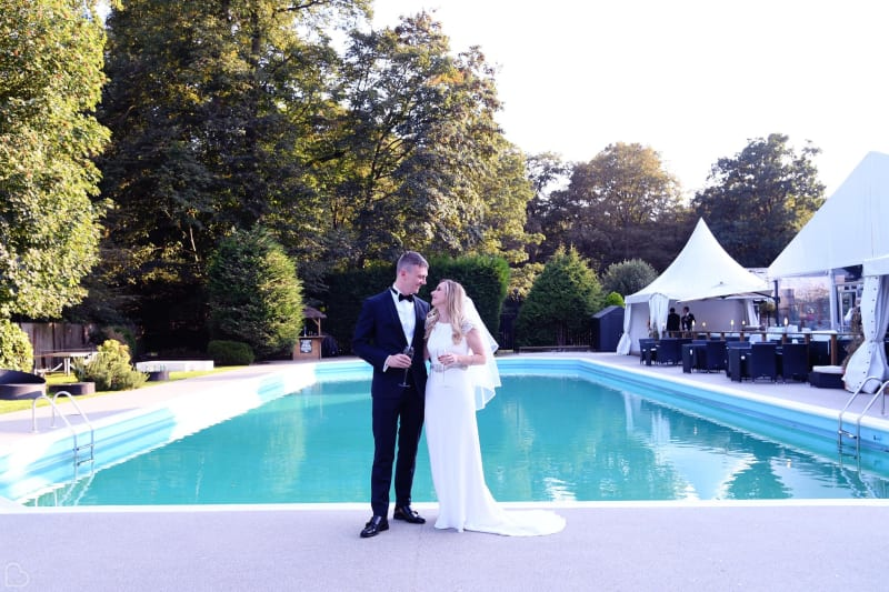 Newlyweds toast in front of the pool at The Kings Oak Hotel