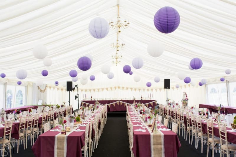Wedding marquee decorated with lavender paper spheres.