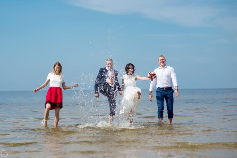 Happy newlyweds and their friends dip their feet in the ocean.