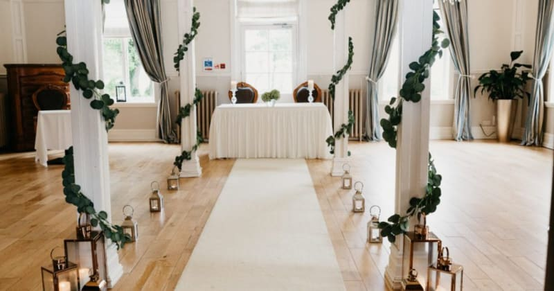 Image of ceremony room. Pillars down aisle with ivy wrapped around, a white aisle and table at the end with two chairs