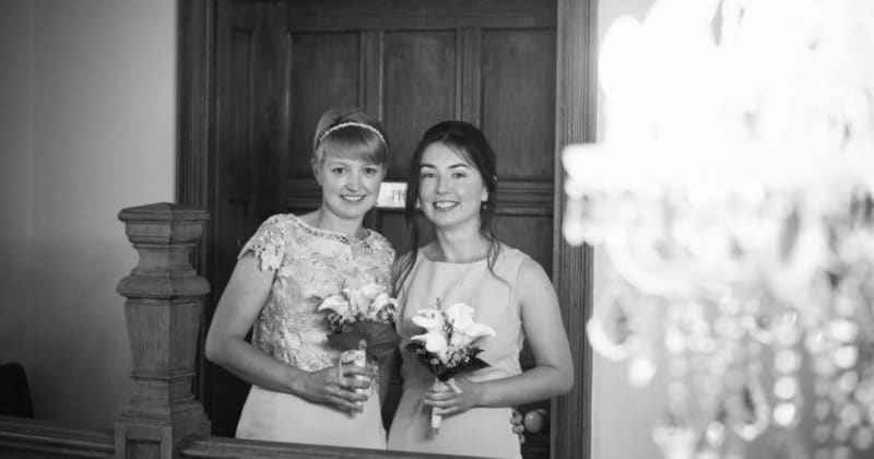 Black and white picture of brides smiling, holding bouquets inside house, in front of a closed wooden door