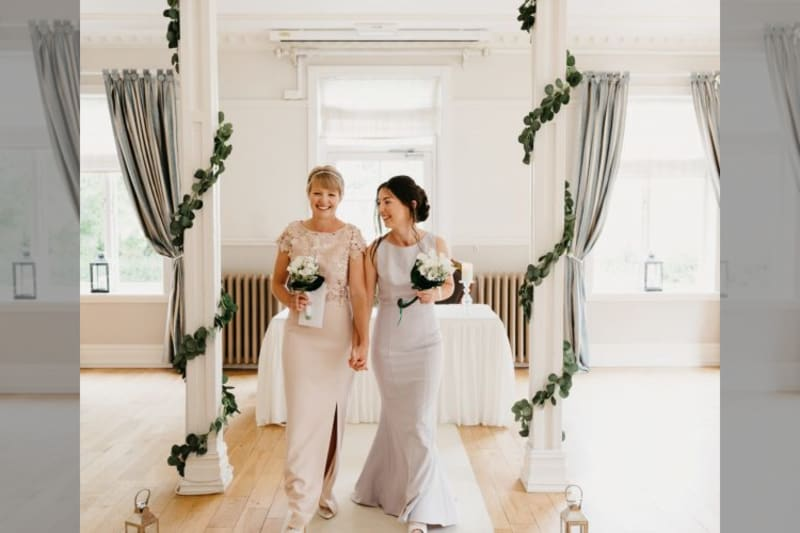 Brides walking down aisle with bouquets, smiling after ceremony