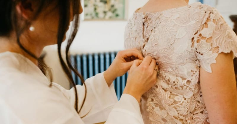Bride doing up the buttons at the back of lace blush dress of other bride