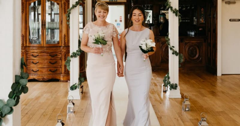 Brides holding hands, walking down aisle holding bouquets of white flowers