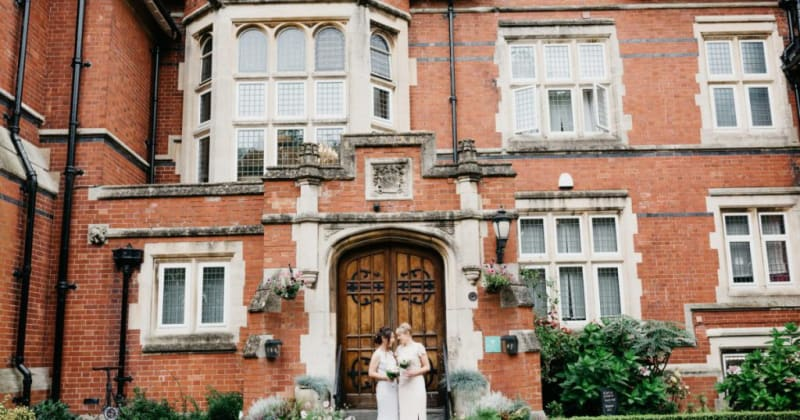 Brides outside large old building, smiling at each other with their bouquets in hand