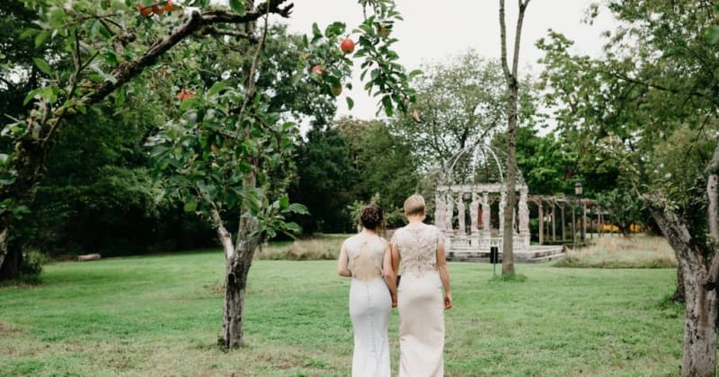 Brides walking into garden, backs of lace dresses showing