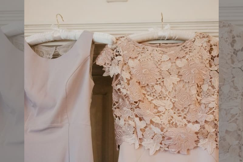One lace blush pink dress on a hanger and one lilac dress on hanger, no sleeves