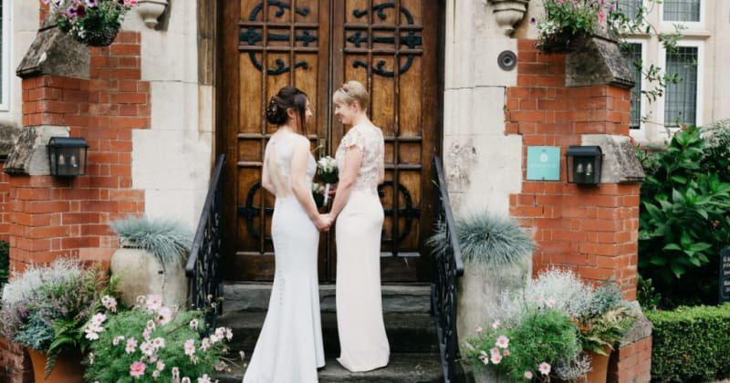 Brides outside wooden doors of Berwick Lodge, looking at each other smiling, holding hands.