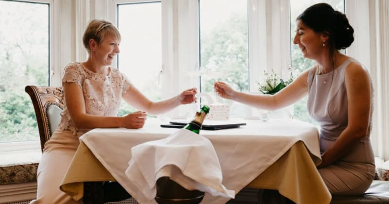 Brides smiling, sitting at table toasting with champagne.