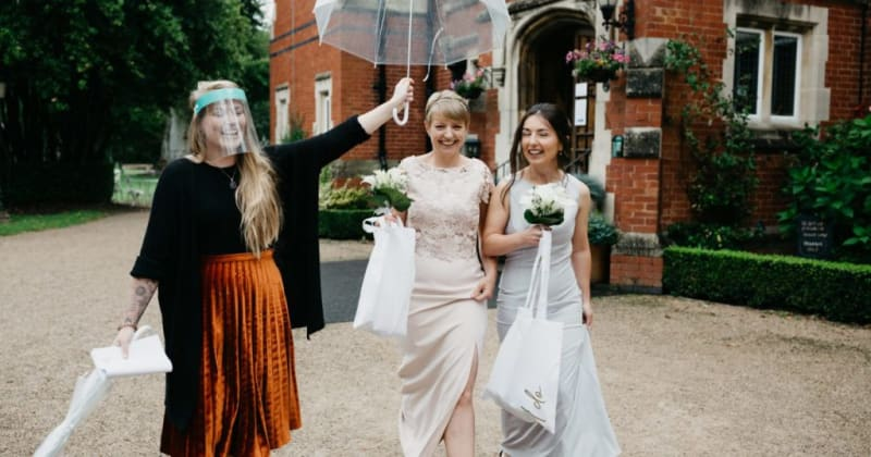 Celebrant and brides standing outside. Celebrant smiling, holding clear umbrella over the happy couple
