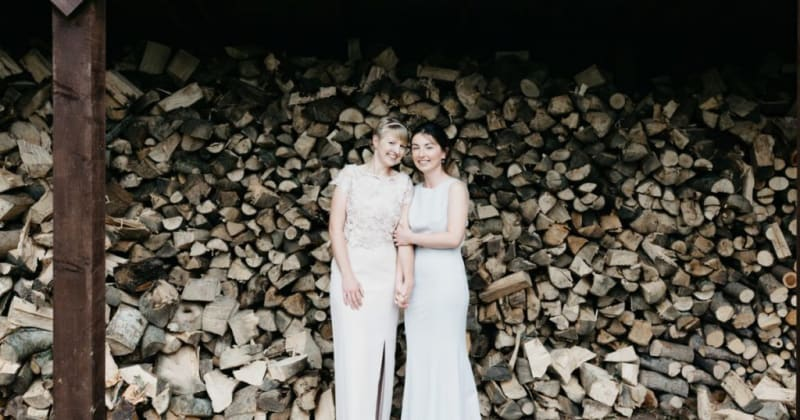 Brides smiling, holding hands in front of large stack of logs