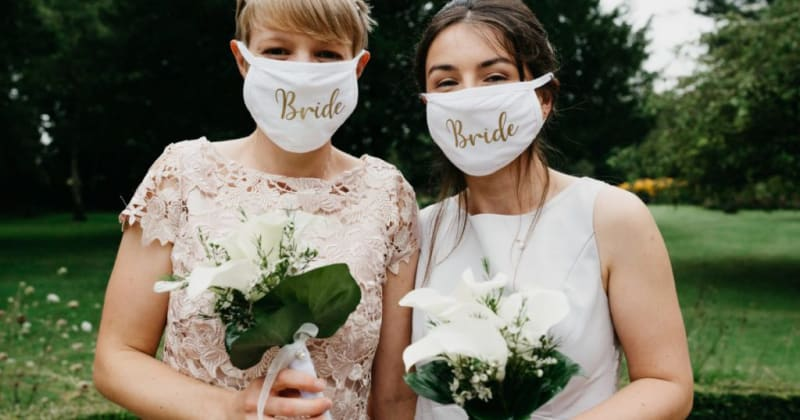 Brides smiling for camera in garden holding bouquets. Brides wear face masks with 'Bride' written on in gold