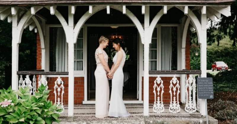 Brides holding hands facing each other outside quaint white and red-brick lodge