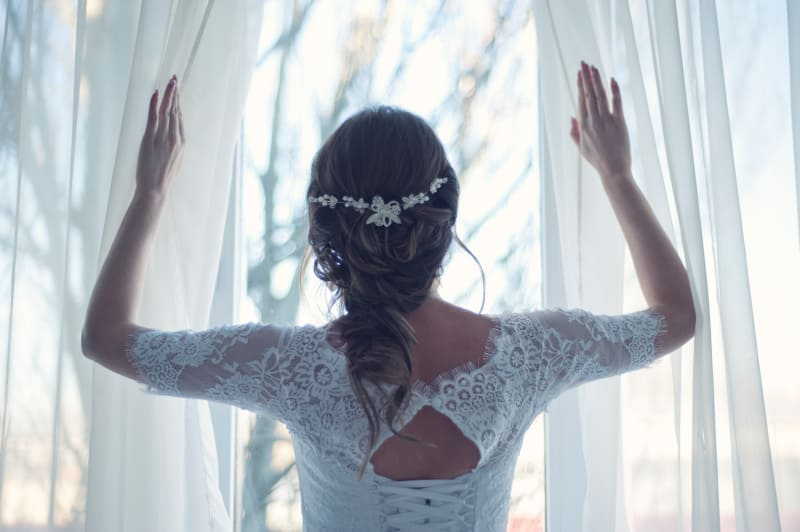 Bridebook.co.uk bride opening curtains