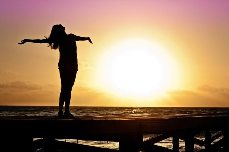 Woman being very happy by sea at sunet