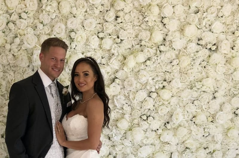 White flower wall with married couple standing in front of flower wall