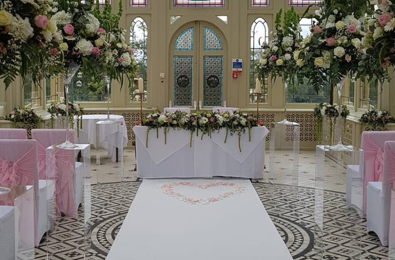 Lovely pink, white and yellow hanging flowers hung from ceiling of wedding venue above the wedding chairs