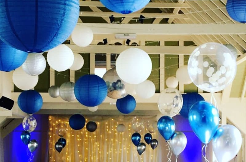 Blue and white custom balloons near the ceiling of wedding venue