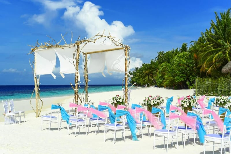 Pink and blue ribbons tied to wedding chairs at beautiful beach wedding
