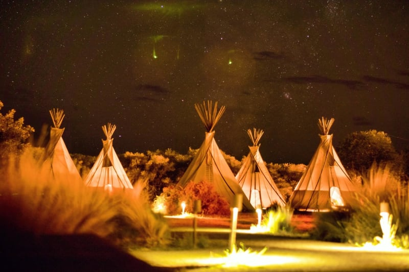 Glamping engagement party with tipis outdoors at night