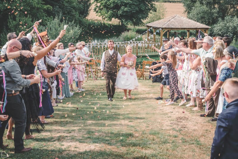 a happy couple celebrates at furtho manor farm wedding venue