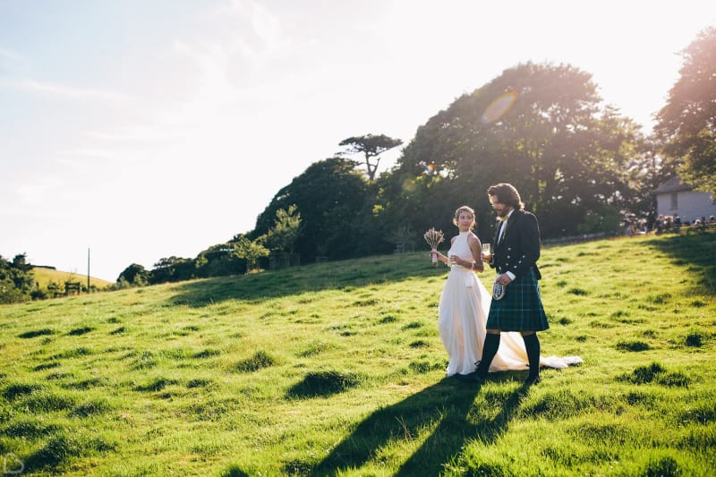 newlyweds walk down a green hill on a sunny day at trenderway farm