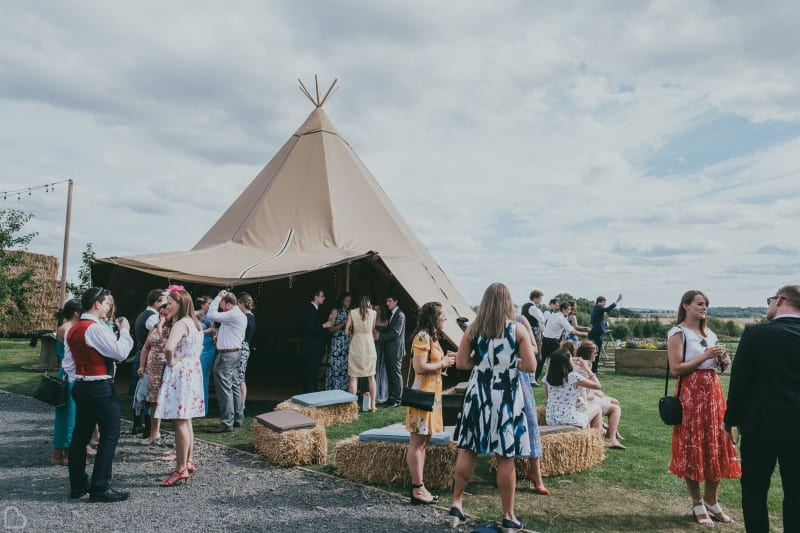 wedding guests relaxing in from of teepee at vallum farm wedding venue