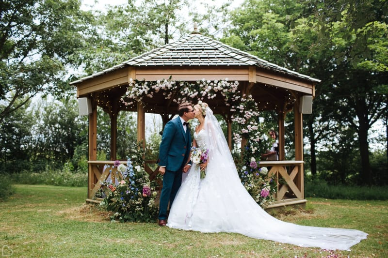 newlyweds kiss in front a gazeebo at crockwell farm