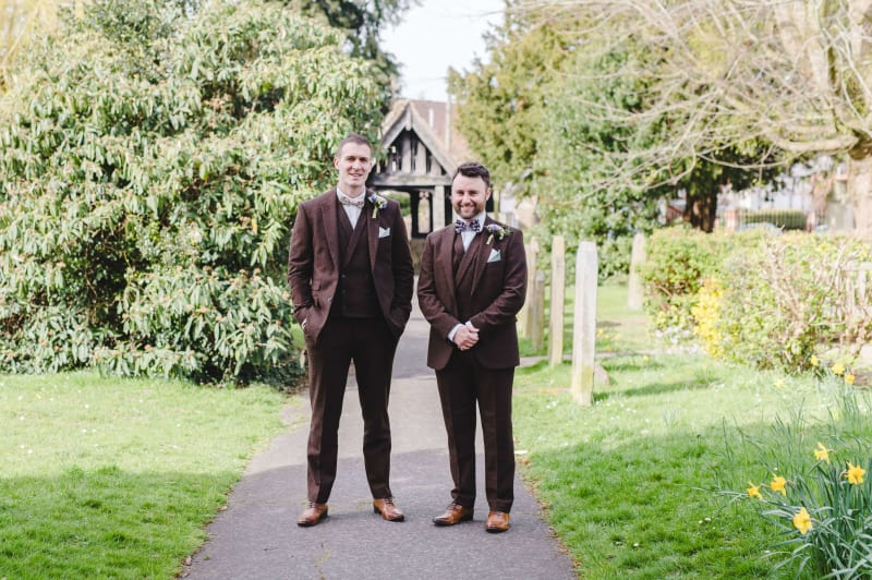 Adam and his best man standing outside the wedding venue in their wedding suits