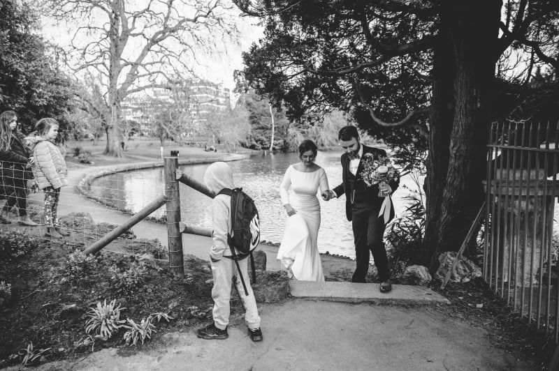 Faye and Adam Hughes walking in a park on their wedding day